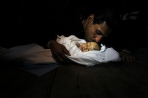 Palestinian-relatives-mourn-over-the-body-of-Hanen-Tafish-a-10-month-old-girl-killed-in-an-Israeli-air-strike-in-the-Zeitun-neighbourhood.-AFP-300x199.jpg